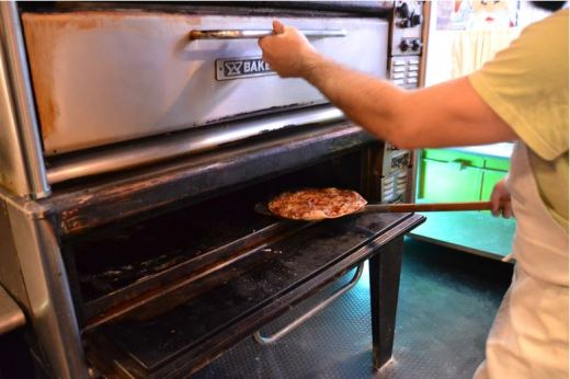 A cook puts a new pizza into the oven at Pizza house on Commercial Street in Springfield, Mo.