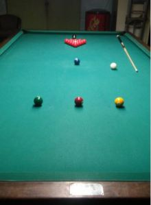 A snooker table has 14 red balls and numbered balls 2-7, each ball having a specific place on the table. Although it isn't shown, the yellow 2 ball, red 4 ball and green 3 ball all sit on a line that is part of a half circle. This is the break circle. The cue ball is placed here when the shooter breaks the rack and also after a scratch. Further down, you see the blue 5 ball, and in the middle of the rack is a pink 6 ball. In the very back is the black 7 ball. As you can see, the pockets are much smaller, and the table longer and wider, than a standard billiards table.